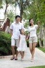 Pais chineses com a filha andando e apontando para a estância turística — Fotografia de Stock