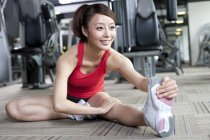 Chinese woman stretching at gym — Stock Photo