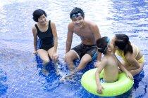 Китайская семья весело и позирует в бассейн — стоковое фото