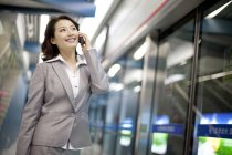 Chinese businesswoman talking on phone at subway station — Stock Photo