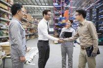 Бизнесмен пожимает руку инженеру на заводе — стоковое фото