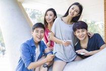 Amici cinesi che tiene smartphone e guardando a porte chiuse — Foto stock