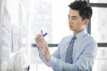 Chinesischer Geschäftsmann mit Whiteboard im Büro arbeiten — Stockfoto