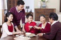 Joyeuse famille multi-génération faire des raviolis chinois — Photo de stock