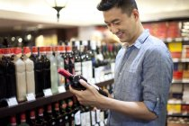 Chinese man choosing wine in supermarket — Stock Photo