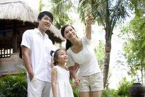 Китайские родители с дочерью стоят и указывают на туристический курорт — стоковое фото