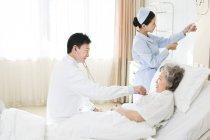 Китайський лікар, використовуючи стетоскоп пацієнта у лікарні — стокове фото
