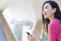 Китаянка слушает музыку на улице — стоковое фото