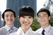 Chinese business professionals in front of skyscraper, portrait — Stock Photo