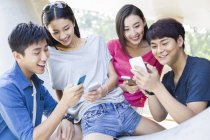 Chinese friends using smartphones on street — Stock Photo