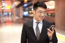 Chinese businessman using smartphone at train station — Stock Photo