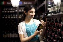 Chinesische Frau Wahl Wein im Keller — Stockfoto