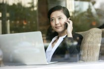Chinese businesswoman talking on phone in cafe — Stock Photo