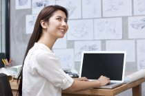 Chinese female designer using laptop in office — Stock Photo