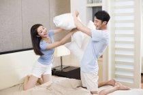 Молодая китайская пара подушки борется в спальне — стоковое фото