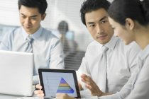 Chinese business team using digital tablet in office — Stock Photo