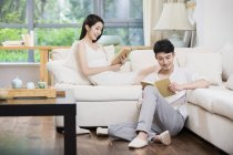 Couple de jeunes chinois lire des livres dans le salon — Photo de stock