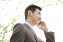 Chinese businessman talking on phone outdoors — Stock Photo