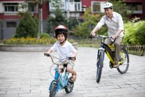 Chinese father and son riding bicycles in residential district — Stock Photo