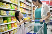 Chinese mother and daughter shopping in supermarket — Stock Photo