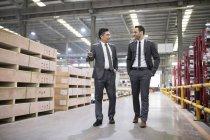 Negócios falando enquanto inspeciona fábrica industrial — Fotografia de Stock