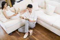 Молодой китайский пару чтения книг в гостиной — стоковое фото