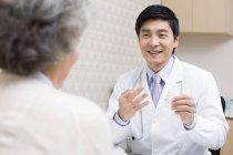 Китайский врач, объясняя дозировка медицины для пациента — стоковое фото