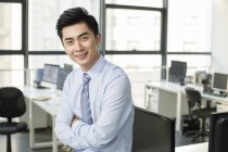 Chinese businessman standing with arms folded in office — Stock Photo