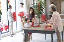Abuela con los niños y la madre que el año nuevo chino papel cortado - foto de stock