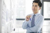 Chinesischer Unternehmer denken am Whiteboard im Büro — Stockfoto