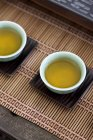 Close-up of tea in chinese cups on bamboo slips — Stock Photo
