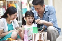 Chinese parents surprising daughter with gift in shopping mall — Stock Photo