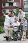 Chinese family with grandfather in wheelchair standing on street and looking at view — Stock Photo