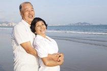 Chinesisch senior pärchen umarmen auf strand — Stockfoto