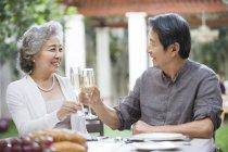 Старшая китайская пара, звенящая на флейте шампанского — стоковое фото