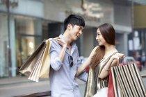 Китайская пара смотрит друг на друга во время покупок на улице — стоковое фото