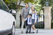 Senior Chinese couple with grandchildren on street — Stock Photo