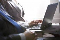 Gente de negocios trabajando con el ordenador portátil en avión, vista recortada - foto de stock