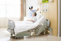 Chinese nurse changing saline drip in patient room — Stock Photo