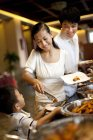Chinese mother helping son at hotel buffet — Stock Photo