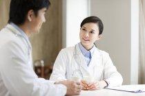 Médecins chinois parlant à la table de l'hôpital — Photo de stock