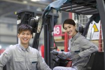 Chinese workers posing with forklift in factory — Stock Photo