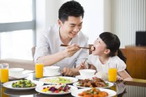 Chinese father feeding daughter with chopsticks at dinner table — Stock Photo