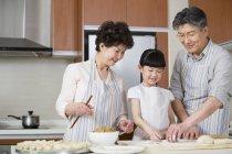 Китайская бабушка и дедушка и внучка приготовления пельменей в кухне — стоковое фото