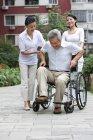 Homme chinois senior debout depuis un fauteuil roulant avec des femmes dans la rue — Photo de stock