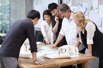 Multi-ethnischen Gruppe von Architekten, die mit Blaupausen — Stockfoto