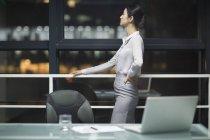 Китайская предпринимательница смотрит в окно в офисе — стоковое фото