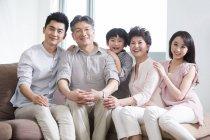 Retrato de familia feliz chinos de tres generaciones, sentado en el sofá - foto de stock