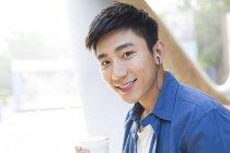 O homem chinês exploração café e ouvindo música em fones de ouvido — Fotografia de Stock