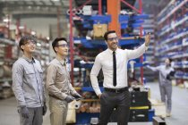 Businessman and Asian engineers talking at factory — Stock Photo